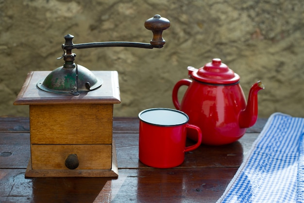 Retro old coffee grinder with vintage red teapot