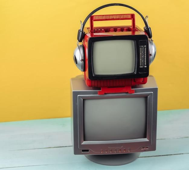 노란색 파란색 배경에 헤드폰이 달린 복고풍의 오래된 휴대용 미니 tv.