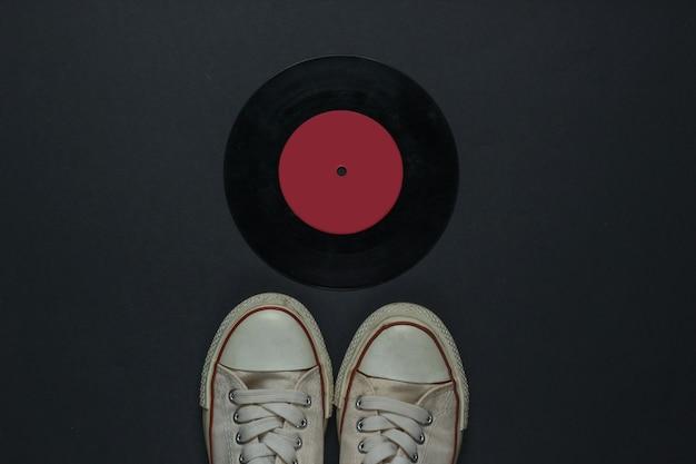 Ретро старые кроссовки и виниловая пластинка на черном фоне. 80-е гг. вид сверху