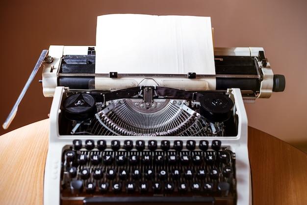 Retro old typewriter with paper sheet, close up photo