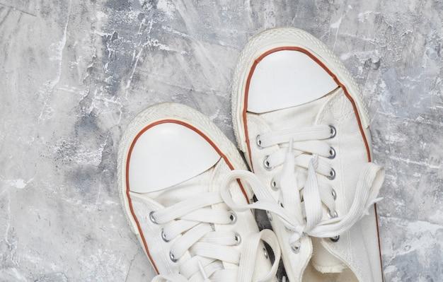 灰色のコンクリートの床にレトロな古い白いスニーカー。上面図。