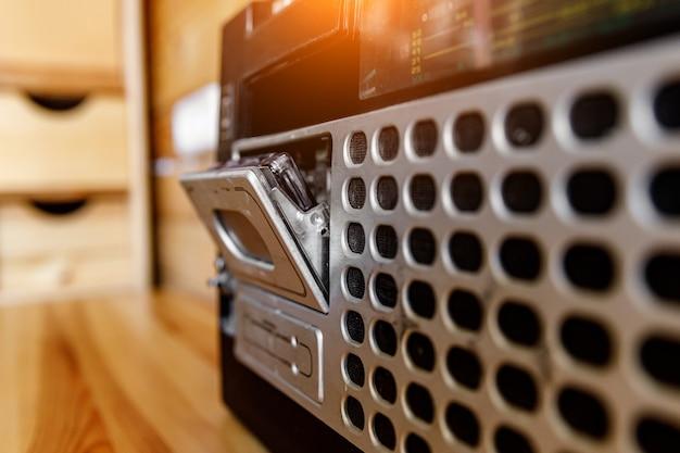 Магнитофон магнитолы радио ретро oldschool дизайна на деревянном столе.