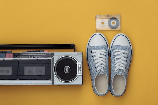 노란색 배경에 복고풍의 구식 휴대용 스테레오 라디오 카세트 레코더, 운동화, 오디오 카세트. 평면도. 플랫 레이 80년대