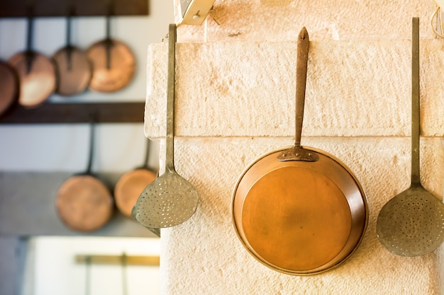 Ретро кастрюля и другая посуда на стене крупным планом