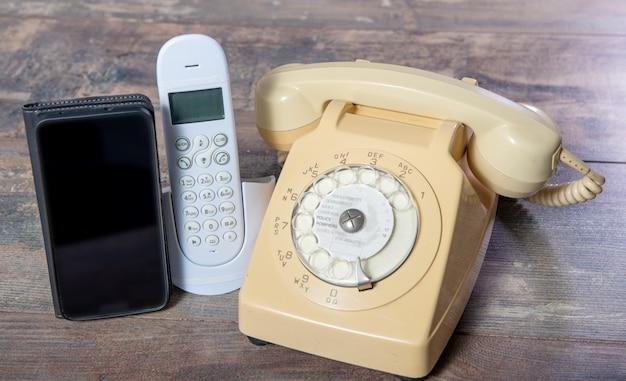 木の板にレトロな電話と新しい携帯電話