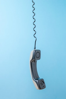A retro phone handset hanging on a stretched wire. retro communication equipment.