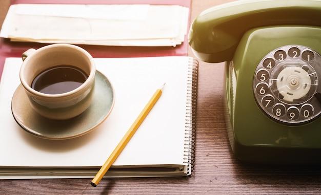 レトロな電話、ノートブック、コーヒーカップ