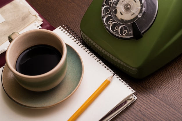 Retro phone, notebook and coffee cup