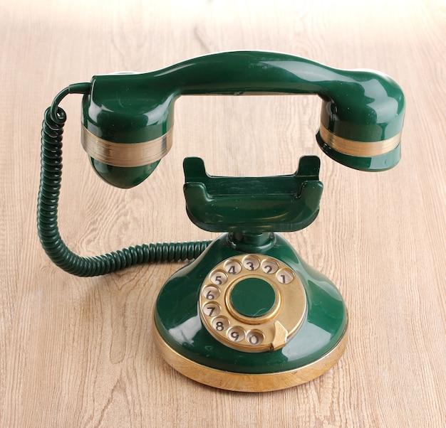 나무 테이블에 떠있는 송수화기와 레트로 전화