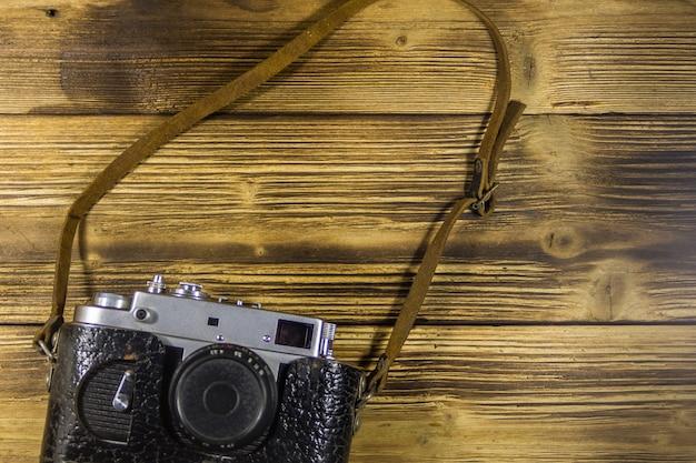 Ретро фотоаппарат в кожаном футляре на деревянном фоне. вид сверху