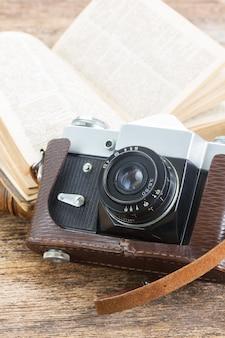 木製のテーブルの上の本とレトロな写真カメラ