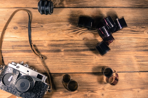 Retro photo camera with photo film and lens on wooden table. top view