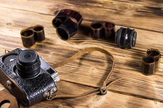 Retro photo camera with photo film and lens on wooden table