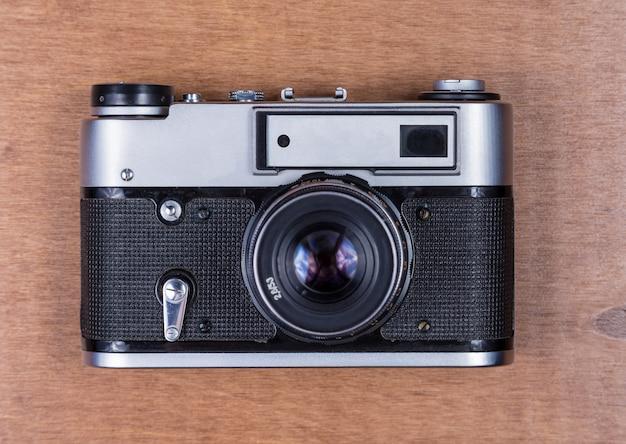 Retro photo camera on a wooden desk
