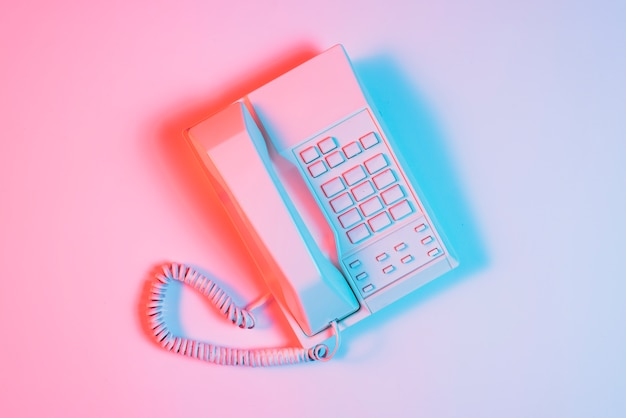 Retro pink telephone with blue light on pink surface