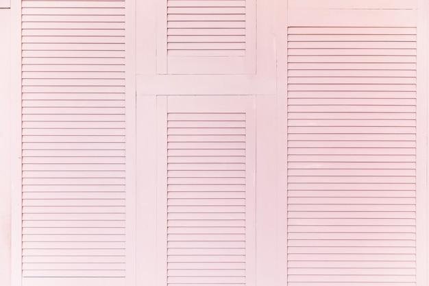 レトロなピンクの木製の背景。ピンクの木製ブラインド