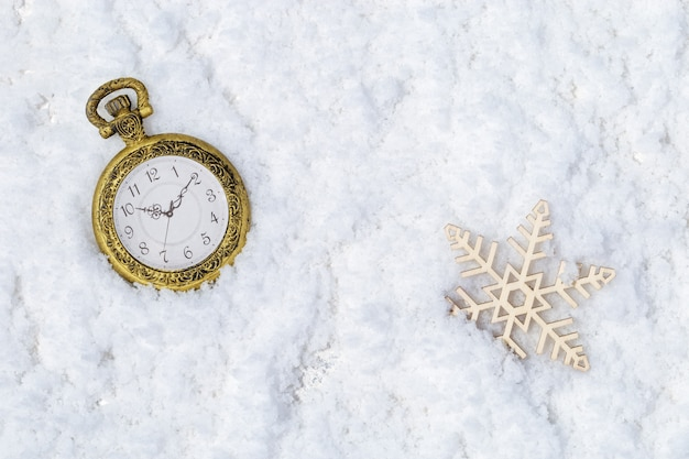 Retro pocket watch and wooden snowflake on snow background. christmas and new year concept.
