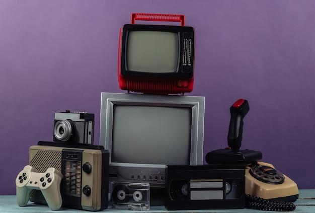 레트로 휴대용 미니 tv 세트, 라디오 수신기, 조이스틱, 게임 패드, 오디오 및 비디오 카세트, 보라색 배경에 전화. 속성 80년대, 레트로 미디어