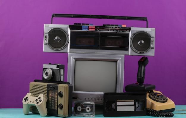 레트로 휴대용 미니 tv 세트, 라디오 수신기, 레코드 플레이어, 조이스틱, 게임 패드, 오디오 및 비디오 카세트, 보라색 배경에 전화. 속성 80년대, 레트로 미디어, 엔터테인먼트