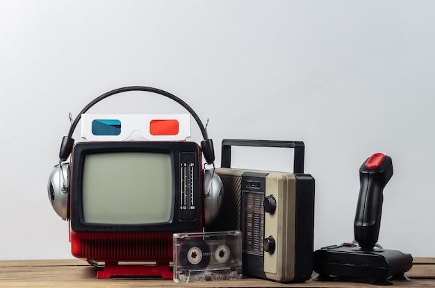 Ретро портативный мини-телевизор с наушниками, 3d-очками, радиоприемником, джойстиком, аудиокассетой на белом фоне. атрибуты 80-х, ретро-стиль