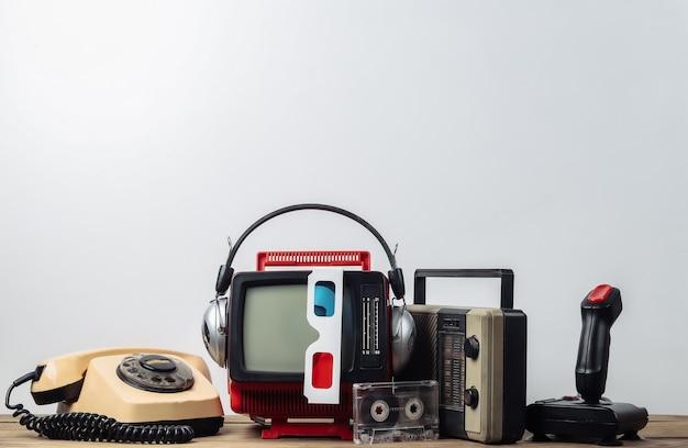 Ретро портативный мини-телевизор с наушниками, 3d-очками, радиоприемником, джойстиком, телефоном, аудиокассетой на белом фоне. атрибуты 80-х, ретро-стиль