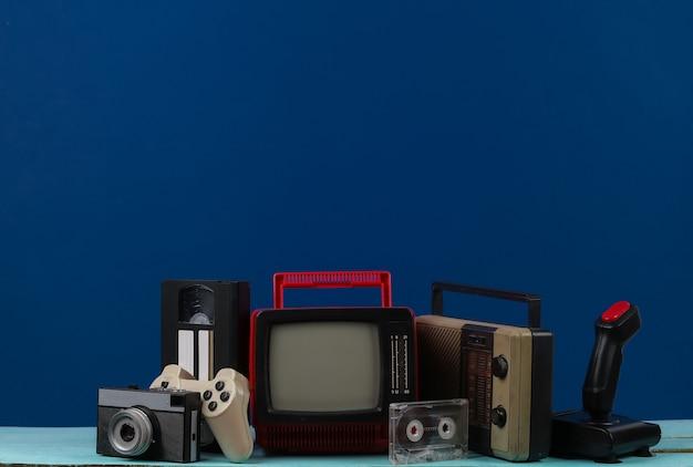 헤드폰, 라디오 수신기, 조이스틱, 카메라, 게임패드, 오디오 및 비디오 카세트, 클래식 파란색 배경의 라디오 수신기가 있는 복고풍 휴대용 미니 tv. 80년대, 레트로 스타일의 속성