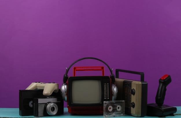 헤드폰, 라디오 수신기, 조이스틱, 게임패드, 오디오 및 비디오 카세트, 보라색 배경에 라디오 수신기가 있는 복고풍 휴대용 미니 tv. 80년대, 레트로 스타일의 속성