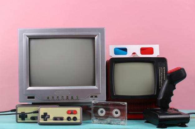 복고풍 휴대용 미니 tv, 조이스틱, 게임 패드, 분홍색 배경의 3d 안경. 속성 80년대, 레트로 미디어, 엔터테인먼트