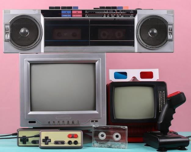 복고풍 휴대용 미니 tv, 레코드 플레이어, 조이스틱, 게임 패드, 분홍색 배경의 오디오 카세트. 속성 80년대, 레트로 미디어, 엔터테인먼트