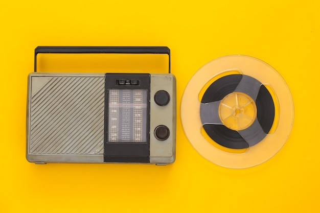 Retro portable radio receiver and audio magnetic tape reel on yellow