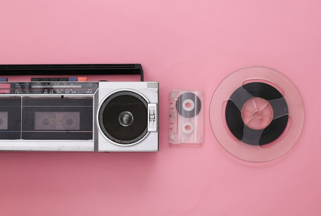 Retro portable stereo cassette recorder, audio cassette and magnetic tape reel on pink