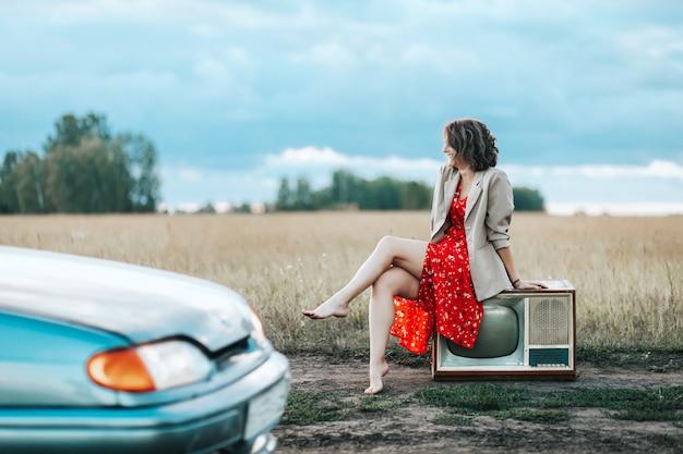 Ретро-портрет молодой женщины в красном платье и бежевой куртке сидит на старом телевизоре