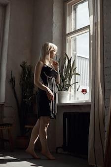 검은 드레스에 복고풍 초상화 섹시 한 금발 여자, 창에서 포즈를 취하는 빈티지 인테리어 여자. 관능적 인 낭만적 인 모습, 소녀는 집에서 휴식을 취합니다.