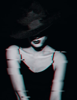 Retro portrait of a woman in a dress and a classic hat on a dark background