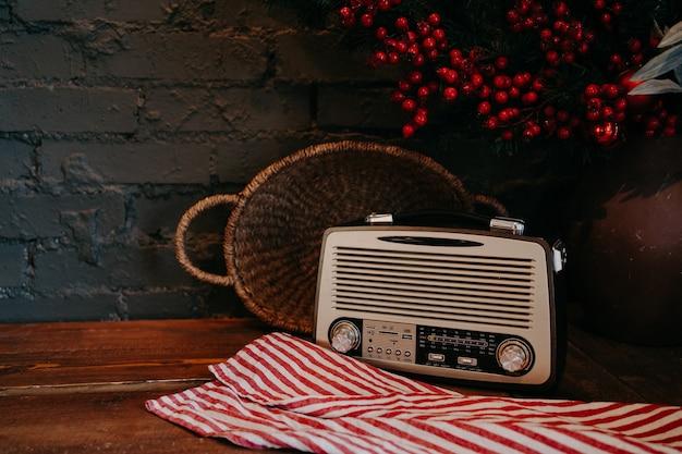 籐のバスケットと花の装飾が施された木製のテーブルのレトロなラジオ。ビンテージ・スタイル。素朴な背景のアンティークの古い放送ラジオ受信機。
