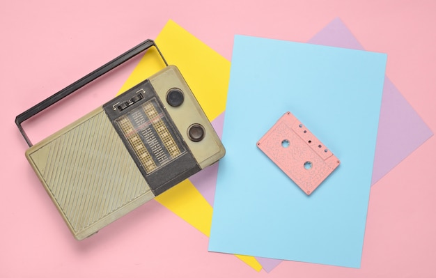 Retro radio receiver, audio cassette on a colored paper background. minimalism. top view