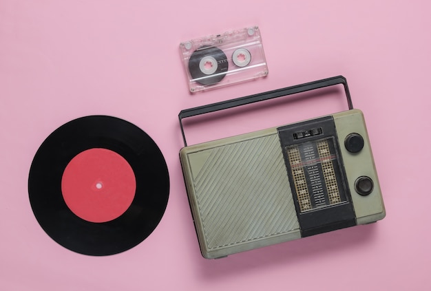 Retro radio receiver oldfashioned vinyl record audio cassette on a pink pastel background