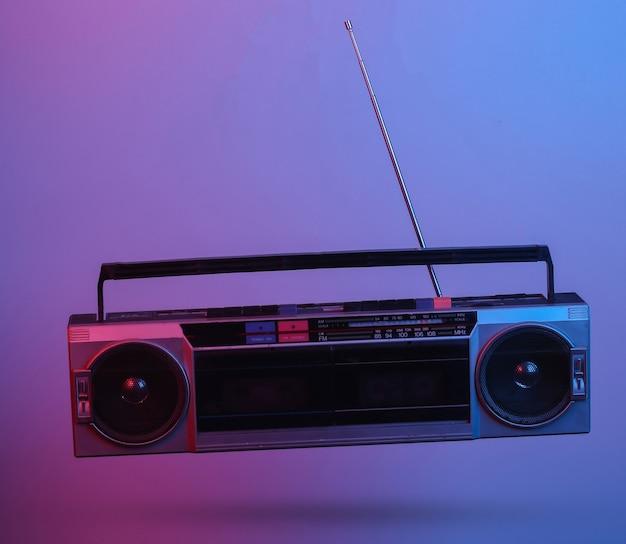Retro radio tape recorder. in blue-red neon gradient light. pop culture. 3d photo. 80s retro wave. minimalism