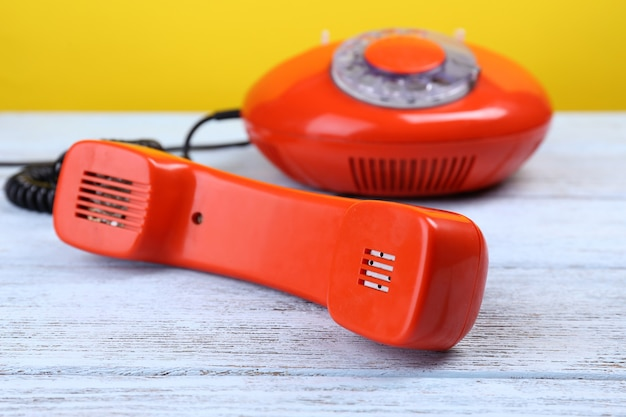 Retro red telephone on color surface, close up