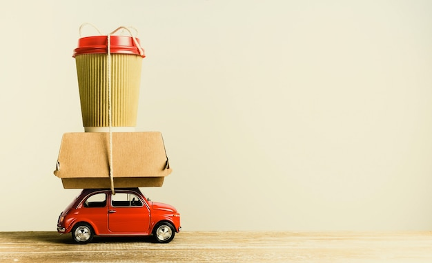 Ретро красный игрушечный автомобиль, доставляющий заказ еды на деревянный стол. ретро тонировка. копировать пространство