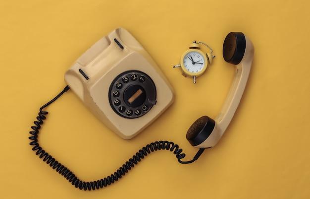 노란색 배경에 복고풍 회전식 전화기와 미니 알람 시계.