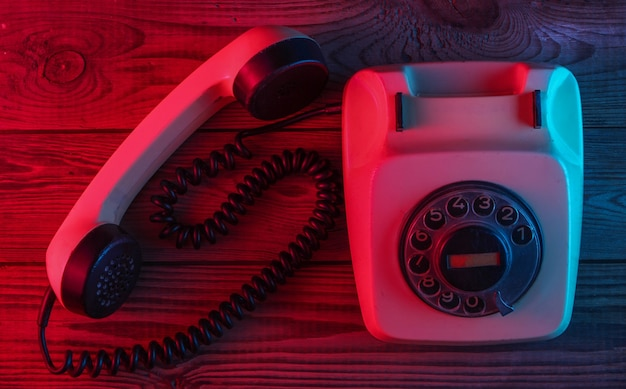 Retro rotary telephone on a wooden surface with red-blue neon light