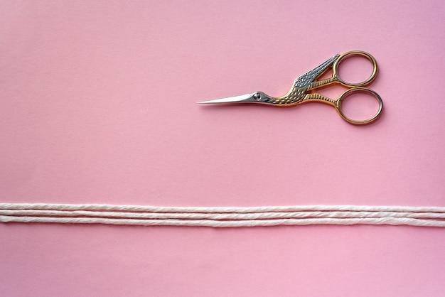 Ретро ножницы из золота и серебра в виде птички на розовом фоне и трех белых хлопковых ниток. ручная работа, швея, портниха, макраме, вышивка.