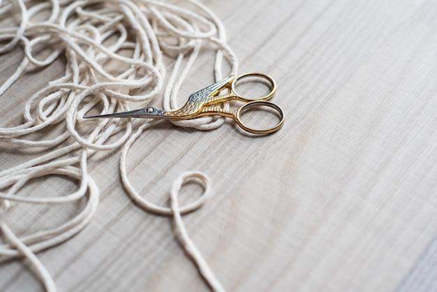 Ретро ножницы из золота и серебра в виде птицы на фоне деревянной текстуры и трех белых хлопковых ниток. ручная работа, швея, портниха, макраме, вышивка.