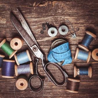 Ретро ножницы, текстильные и швейные нитки на деревянном столе