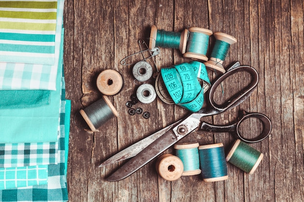 Retro scissors, textile and sewing threads on the wooden table