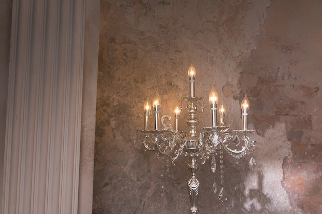 Retro silver candlesticks with white candles on wall.