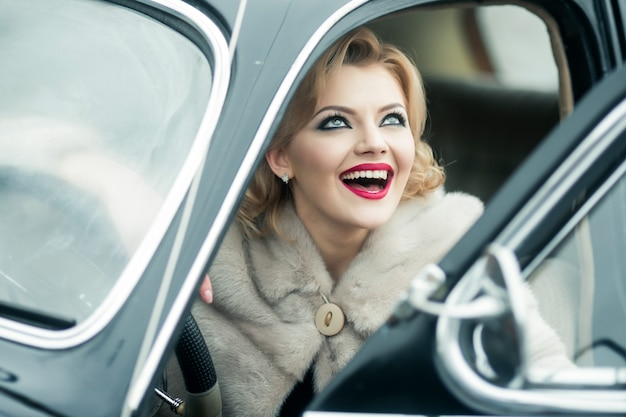 여행에 빈티지 자동차에 레트로 웃는 여자. 레트로 자동차에 앉아 행복 핀 업 모델입니다.
