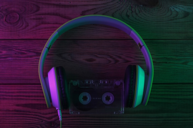 Ретро стерео наушники с аудиокассетой. неоновый фиолетовый и зеленый свет