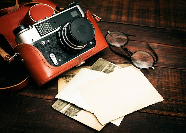 Retro still camera and some old photos on wooden table surface